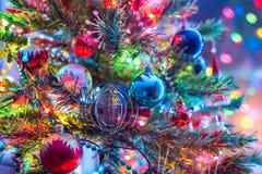 Del av julgranen, med färgrika glass bollar, små garneringar och färgrika ljusa reflexioner Fotografering för Bildbyråer