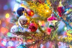 Del av julgranen, med färgrika glass bollar, små garneringar och färgrika ljusa reflexioner Arkivfoto