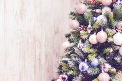 Del av julgranen med leksaker nära den bruna väggen royaltyfri foto