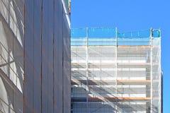 Del av konstruktionsplatsen med materialet till byggnadsställning på flervånings- byggande fasad under renovering royaltyfria bilder