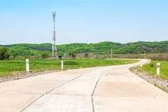 Del av landsvägen av vänd för konkreta tjock skiva mot bakgrunden av sommarträd och buskar bredvid royaltyfria bilder