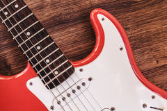 Del av modern elkraft sex röda färg för radgitarr med glansigt fullföljande, uppsamlingar och kontrollknoppar på träbakgrundscl royaltyfri fotografi