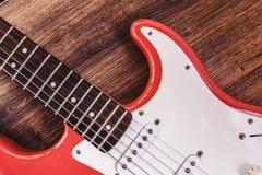 Del av modern elkraft sex röda färg för radgitarr med glansigt fullföljande, uppsamlingar och kontrollknoppar på träbakgrundscl royaltyfri bild