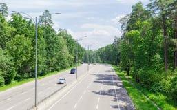Del av motorwayen med skogen på båda sidor i sommar Royaltyfri Fotografi