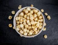 Del av popcorn på en kritiseratjock skiva Royaltyfria Foton