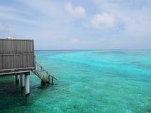 Del av rum för Maldiverna vattenvilla i en ösemesterort som ser wood trappa ner från balkong till havgolvet Royaltyfria Foton