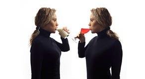 Del av serie Självsamtalbegrepp Ståenden av den unga kvinnan som talar till henne i spegel och att dricka mjölkar eller vin i exp royaltyfri fotografi
