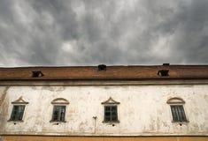 Del av slotten Moravsky Krumlov, Tjeckien Detalj av det gamla huset med den gamla flagade bort fasaden och dramatiska mörka moln  Arkivbilder