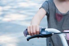 Del av styrninghjulet Barns cykel Hand av barnet p? ett hjul arkivbilder