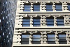 Del av två fasader av höga löneförhöjningbyggnader i New York City med Royaltyfri Fotografi