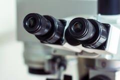 Del av utrustningen för att beskåda små objekt Svarta okular av en yrkesmässig laboratoriummikroskopnärbild Royaltyfria Bilder