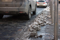 Del av vinterfrosttrottoaren Hög av samlade snö- och höstsidor Kall stadsgata arkivfoton