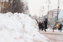 Del av vinterfrosttrottoaren Hög samlade snö- och höstsidor triumfsikt för båge D Arkivfoton