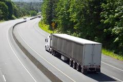 Del blanco remolque largo del camión semi en la vuelta de la carretera Foto de archivo