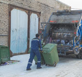 Del camion di immondizia un lavoratore prepara i barilotti di immondizia Fotografia Stock
