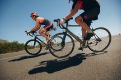 Del ciclista del montar a caballo de las bicicletas colina abajo en la carretera nacional Fotografía de archivo libre de regalías