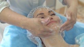 Del cierre cliente de la chica joven para arriba - del salón de belleza durante el tratamiento facial en salón del balneario almacen de metraje de vídeo