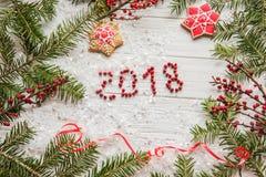 ` 2018 del ` de las bayas de la inscripción entre las ramas de la picea y de las galletas de la Navidad Fotos de archivo libres de regalías