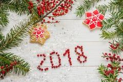 ` 2018 del ` de las bayas de la inscripción entre las ramas de la picea y de las galletas de la Navidad Imagen de archivo