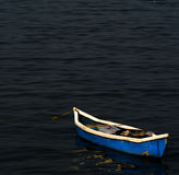 ` Del ` en descanso - un barco azul todo solamente en calmar y las aguas de mar serenas Fotos de archivo libres de regalías
