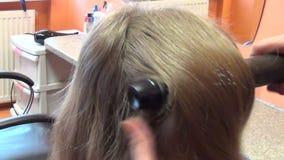 Del enfoque la cabeza y el peluquero de la mujer del cliente hacia fuera hacen que el pelo se viste Foto de archivo