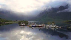 Del enfoque lapso de tiempo hacia fuera de barcos amarrados y de nubes que remolinan alrededor de las montañas metrajes