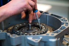 Del för bil för reparationsmanfixande med skruvmejsel Ung mekaniker på hans seminarium royaltyfria foton