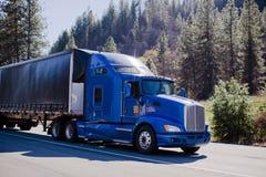 Del famouse del aparejo camión moderno grande semi azul y remolque negro entoldado Fotos de archivo libres de regalías
