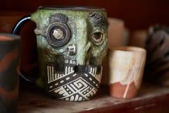 Del fronte tazza fatta a mano spaventosa su uno scaffale di legno, primo piano, profondità di campo del vasaio egualmente dello s immagini stock