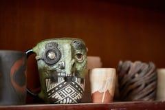 Del fronte tazza fatta a mano spaventosa su uno scaffale di legno, primo piano, profondità di campo del vasaio egualmente dello s immagine stock