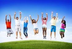 Del grupo de los amigos celebración al aire libre que gana a Victory Jump Concept Imágenes de archivo libres de regalías