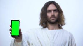 Del hombre smartphone con la pantalla verde, uso móvil de la tenencia de Jesús igualmente de la biblia foto de archivo libre de regalías