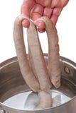 Del imponer salchichas en agua caliente foto de archivo