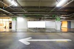 Del parcheggio interno nel sottosuolo con il tabellone per le affissioni in bianco Interno vuoto del parcheggio dello spazio alla Immagini Stock Libere da Diritti
