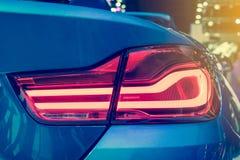 Del primer el coche rojo de la luz de la cola detrás en salón del automóvil Imagenes de archivo