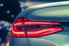 Del primer el coche rojo de la luz de la cola detrás en salón del automóvil Imagen de archivo