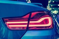 Del primer el coche rojo de la luz de la cola detrás en salón del automóvil Fotografía de archivo