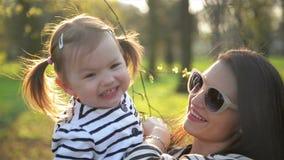 Del primer retrato al aire libre de la madre sonriente y de la hija linda en el parque La morenita hermosa con las gafas de sol s almacen de video