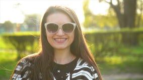 Del primo piano ritratto all'aperto di stupore castana in occhiali da sole e camicia a strisce che esaminano la macchina fotograf archivi video