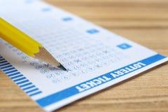 Del relleno boleto de lotería hacia fuera con el lápiz en la tabla de madera, primer imágenes de archivo libres de regalías