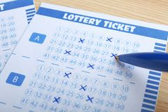Del relleno boletos de lotería hacia fuera con la pluma en la tabla de madera, primer fotografía de archivo