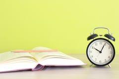 Del reloj libro abierto cerca en fondo verde Imagen de archivo