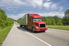 Del rojo camión semi en autopista en primavera Imágenes de archivo libres de regalías