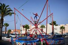 Del Segura, España de Guardamar - 26 de junio de 2016: Los niños en el parque de atracciones saltan arriba en el trampolín imagenes de archivo