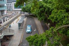 Del taxi parcheggio al passeggero aspettante di arresto del taxi fra gli alberi verdi osservati dal passaggio immagine stock libera da diritti