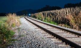 Del tren vías escarpadas inminentes abajo en la noche Fotos de archivo