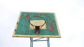 Del viejo baloncesto del aro de la opinión la bola oxidada inferior del deporte del hierro al aire libre entra en la cesta metrajes