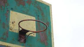 Del viejo del aro baloncesto del deporte de la opinión la bola oxidada inferior del hierro al aire libre entra en la cesta almacen de metraje de vídeo