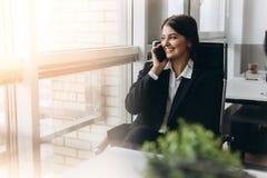Dela bra ekonominyheter Attraktiv ung kvinna som talar på mobiltelefonen och ler, medan sitta på hennes arbetsplats in royaltyfri bild