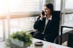 Dela bra ekonominyheter Attraktiv ung kvinna som talar på mobiltelefonen och ler, medan sitta på hennes arbetsplats in royaltyfria bilder